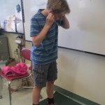 Another student listening to sound which has traveled up a string to his ears.