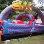 Purple, pink, and yellow racing bouncy house