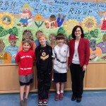 Caden, Kristian, Beck and Mrs. Dayal standing in front of our mosaic mural.