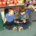 A 5th grade boy reads to a younger student.