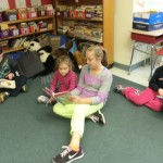 A kindergarten girl reads with her buddy.