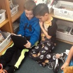 Two second grade boys sharing a book on an iPad.