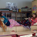 Two fourth grade girls sitting on a counter in their classroom read by themselves.