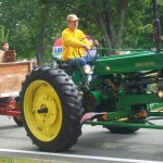 Farm tractor pulling hey wagon with people.