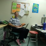 Our technology teacher in his office surrounded by digital devices and a yellow and black Bee-Bott.