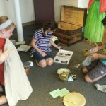 Students investigating items in an Irish immigrant's trunk.