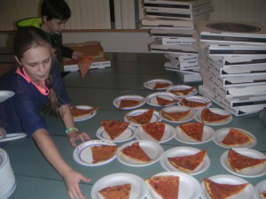 Students grabbing a slice of pizza.