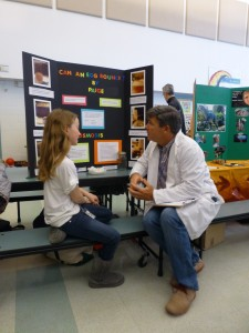 A judge talking with one of the student scientists at the Science Fiar.