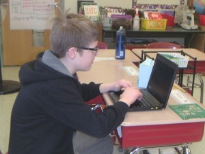 Student, sitting at a desk, using a school ChromeBook.