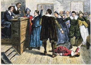 in this scene from the trails one of the afflicted has fallen to the floor. The accused woman standing in front of the judges tries to defend herself.