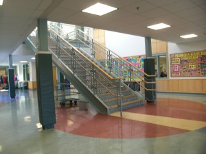 Main staircase in Chickerings lobby showing the large blank wall to the right of the staircase where the new artwork will be installed.