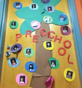 Picture of the Preschool doorway with a tree and pictures of students in colored circles.
