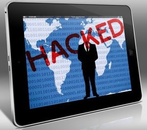 Image of a digital device with the word HACKED written in red across the screen.