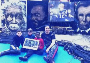 Image of Rob Surette sitting on the floor with 3 Chickering Reporters, displayed behind him are several of his paintings. Left to right: Albert Einstein, Martin Luther King, Jr., Tom Brady, and Abraham Lincoln.