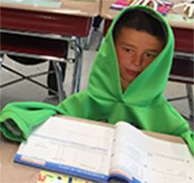 Picture of one of the desk for Open House with student's face inside a hoodie - looks like the students are there.