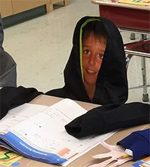 Another 'fake' student in a hoodie sitting at their desk.